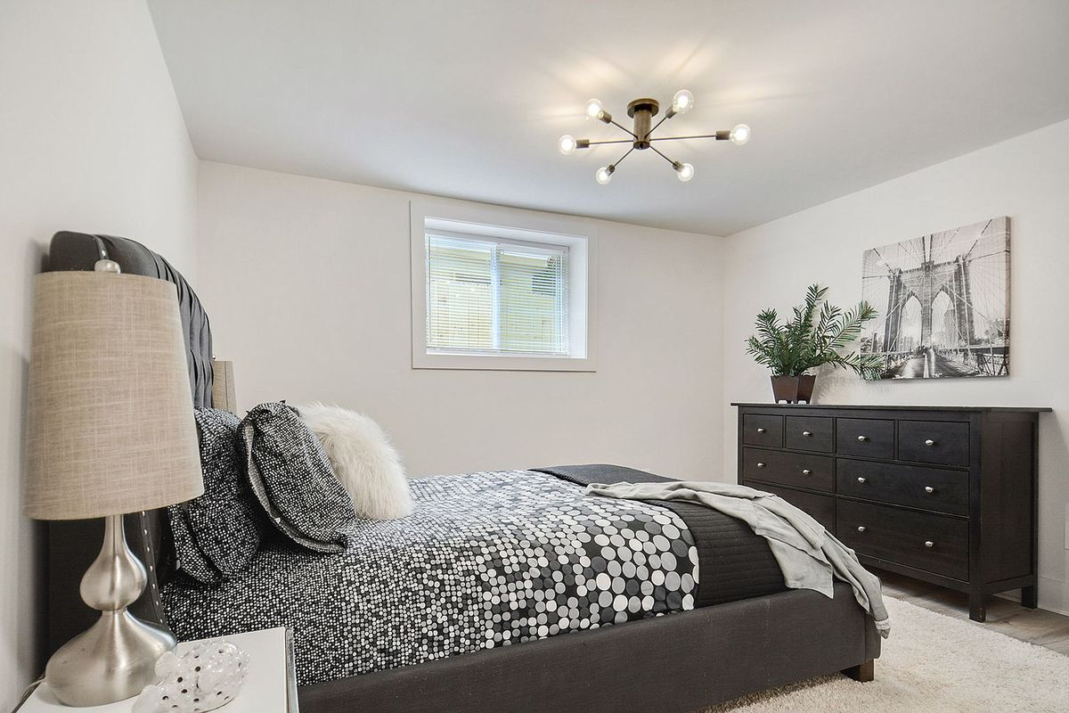 A big white bedroom with a black and white bed.