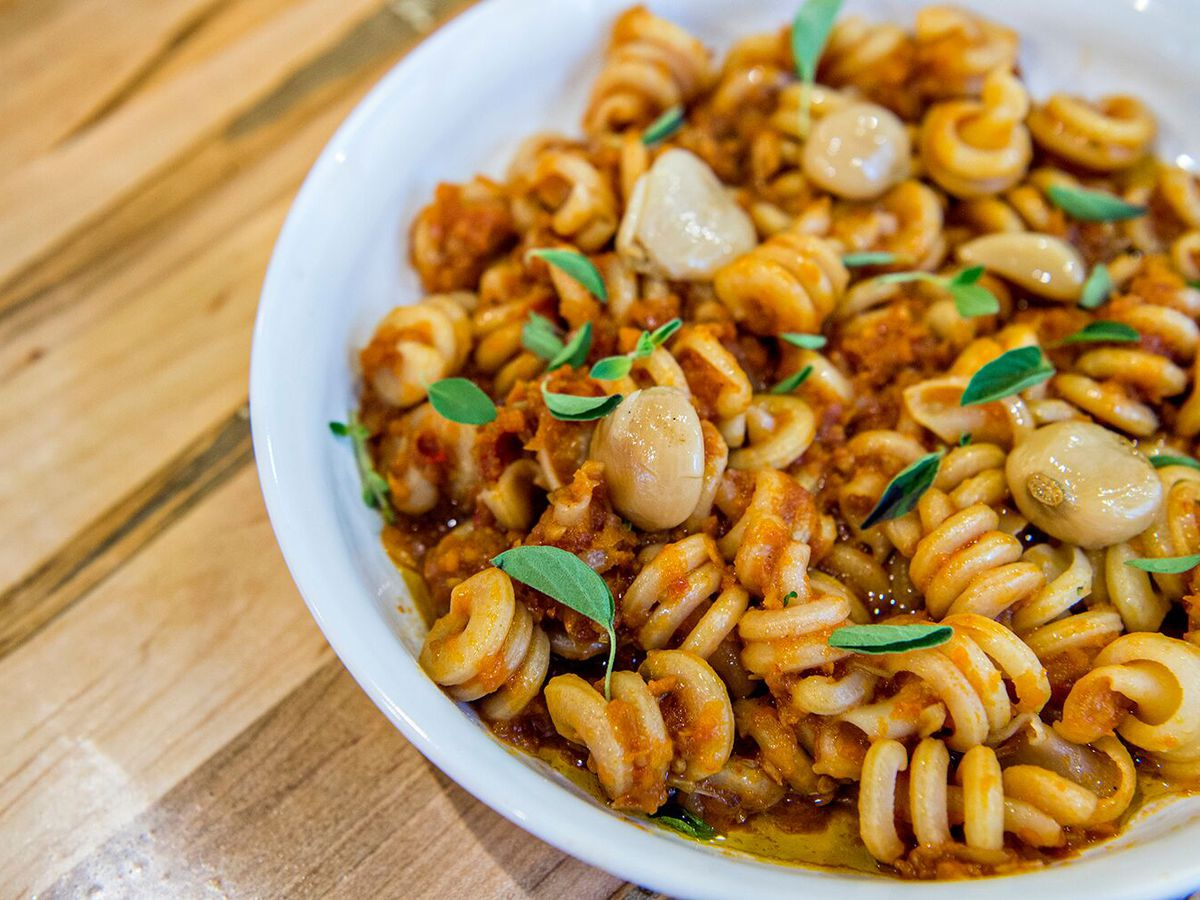 A close up shot of the house-made funghetto pasta with garlic cloves and carrot bolognese at Somebody People