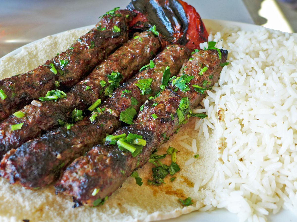 Four ground meat kebabs, nicely charred, on a flatbread with gleaming white rice on the side.