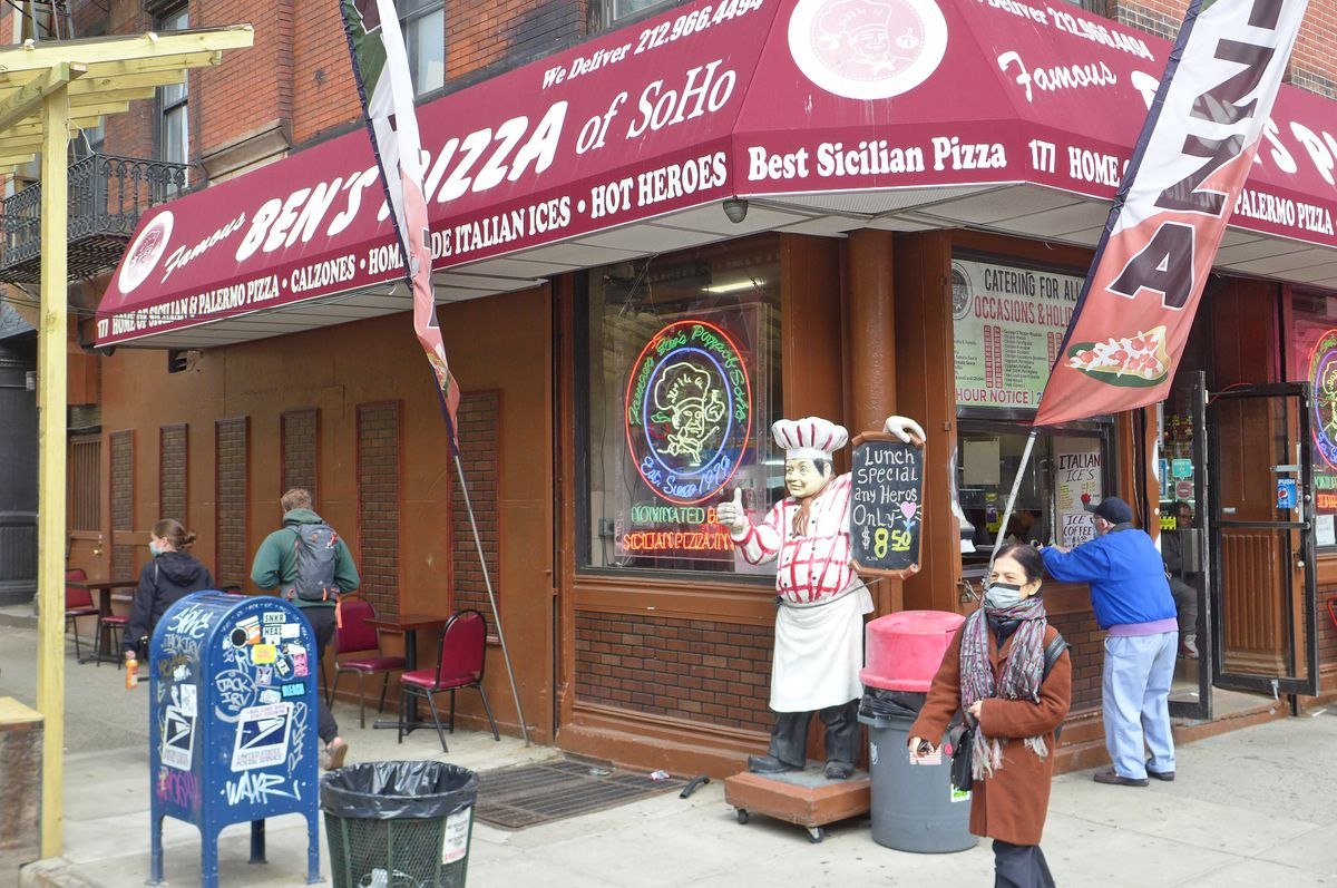 A corner storefront with a red awning and chef figure standing outside and winking.