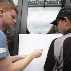 Protesters tape a list of demands onto an entrance to the McDonald's headquarters. | Colin Boyle/Sun-Times