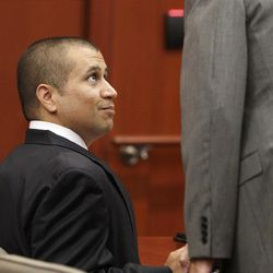 George Zimmerman, left, looks up at his attorney Mark O'Mara in the courtroom, Friday, April 20, 2012, during a bond hearing in Sanford, Fla.