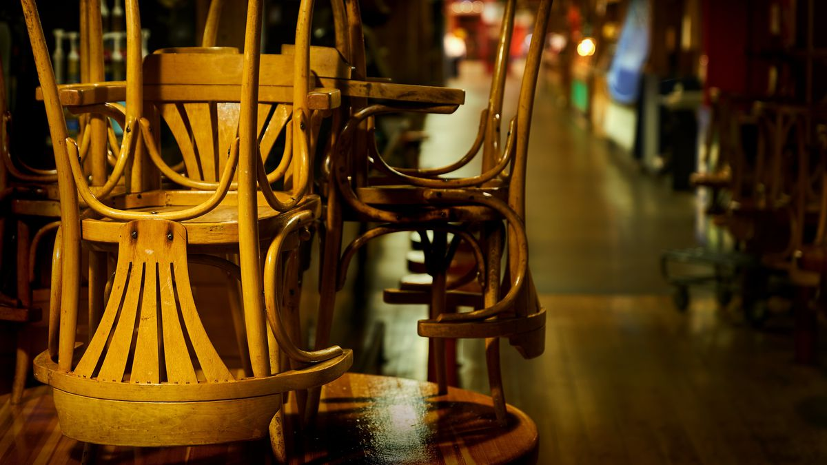 A series of chairs flipped on top of each other on tables to signal the closing of a restaurant at night.