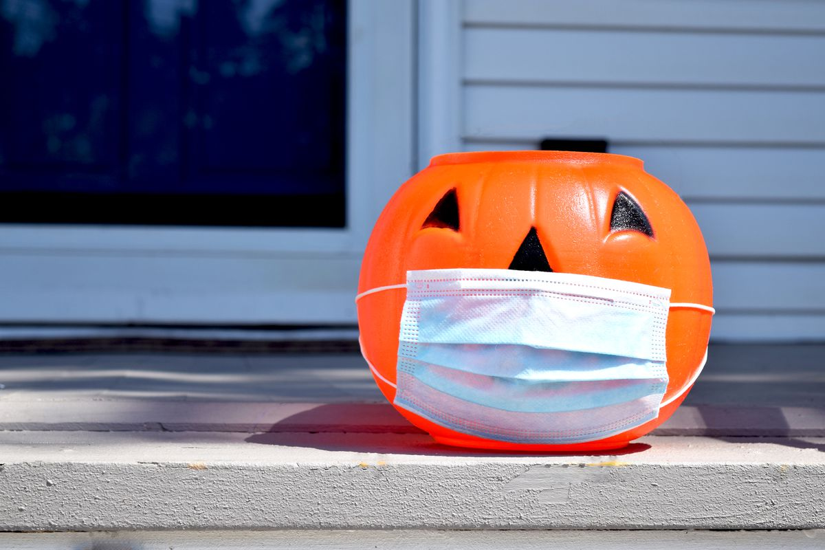 Plastic jack-o-lantern trick-or-treat bucket with a face mask covering the lower half of its face.