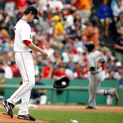 Boston Red Sox's Clay Buchholz, left, throws down his glove as Detroit Tigers' Ryan Raburn, right, rounds third base after hitting a solo home run in the seventh inning.