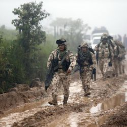 Army soldiers arrive to guard the Mariana Paez demobilization zone, one of many rural camps where FARC rebel fighters are making their transition to civilian life, one day ahead of an event with President Juan Manuel Santos in Buenavista, Colombia, Monday, June 26, 2017.  On Tuesday, Colombia's president will meet the FARC's top commander Timochenko at this camp to commemorate the completion of the disarmament process.