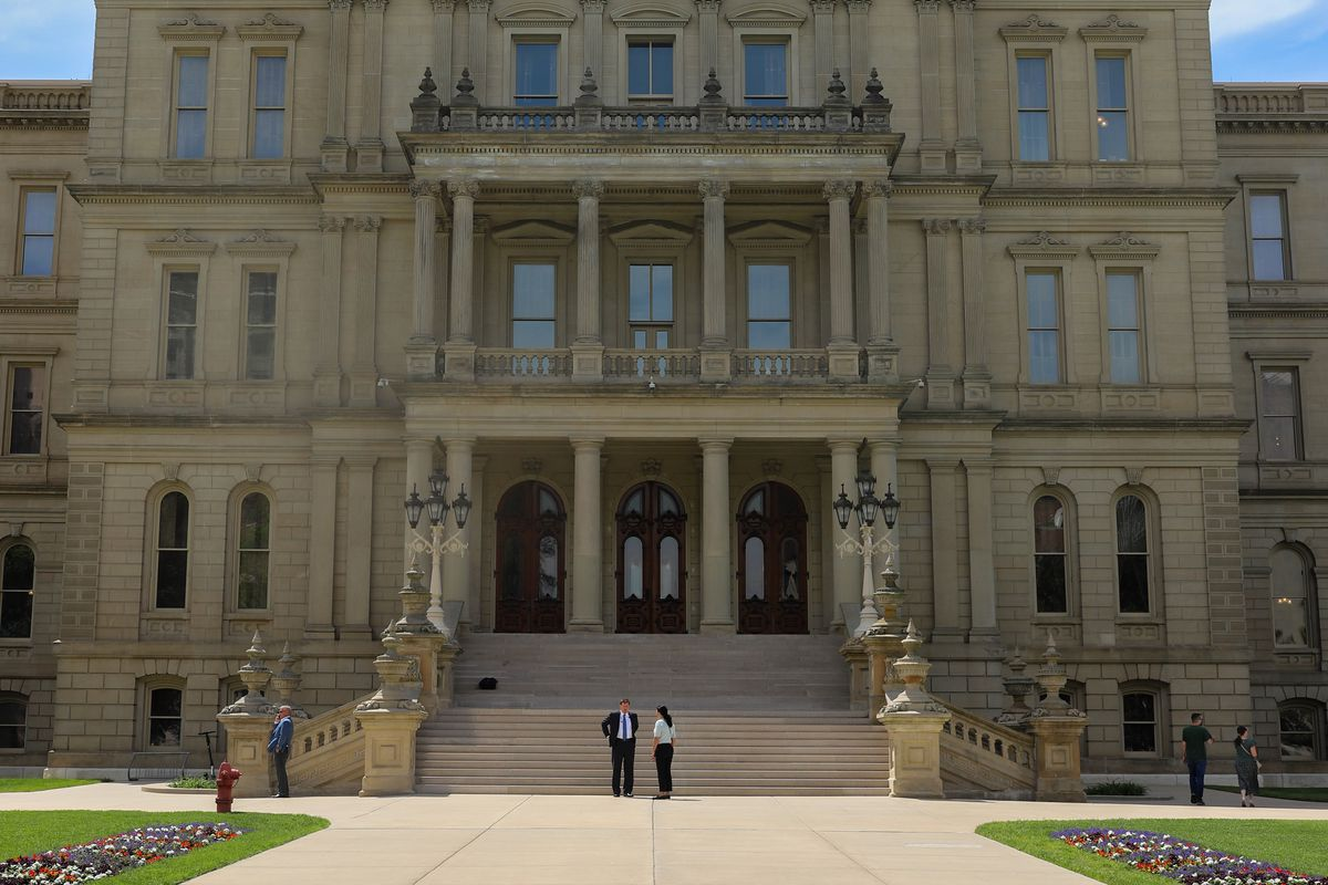 A man and a woman stand in front of the steps of the Michigan capitol in Lansing.