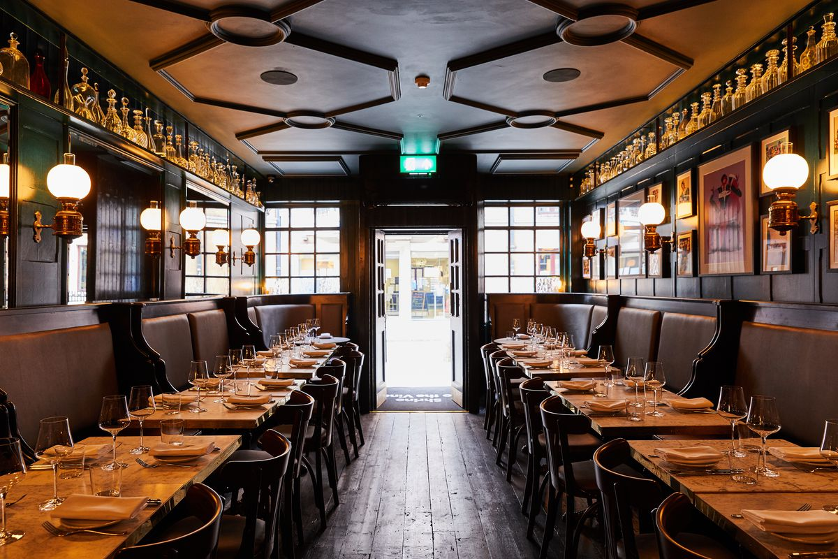 Looking at the interior of Noble Rot Soho towards the front door, with banquettes lined with tablecloths and wine glasses
