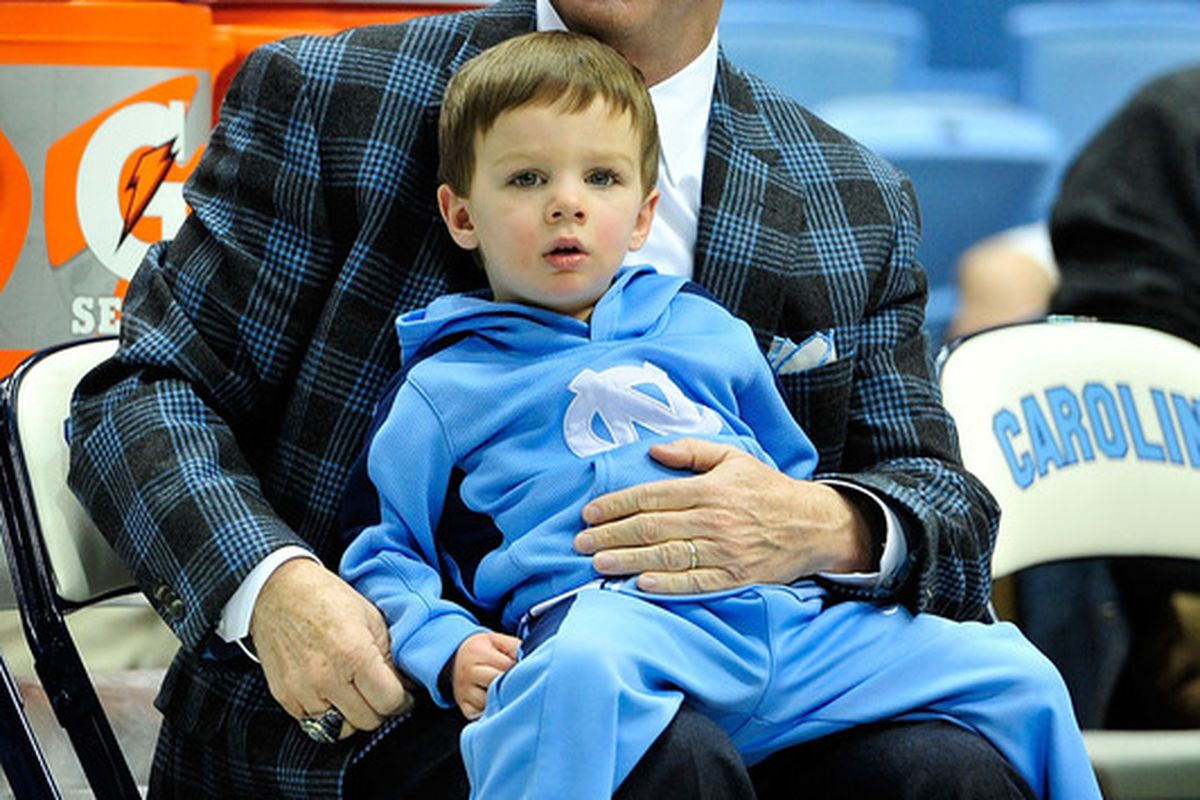 Coach Roy Williams sits with his grandson, Aiden Williams, before a game against the Virginia Cavaliers at the Dean Smith Center. North Carolina won 70-52.