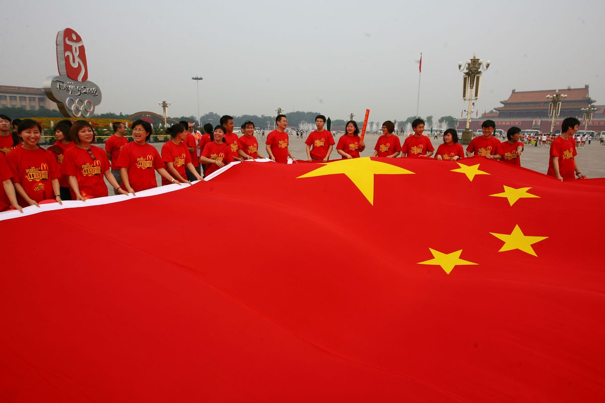 Chinese volunteers unfold a huge Chinese flag