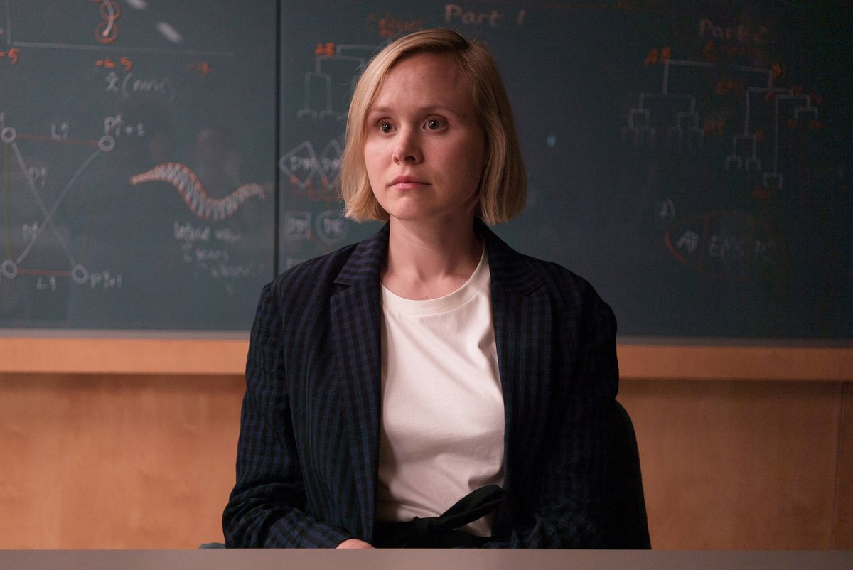 A woman with short blonde hair and a fixed, wide-eyed expression sits staring off-camera in front of a chalkboard covered with diagrams that appear to be programming branch trees and other configurations.