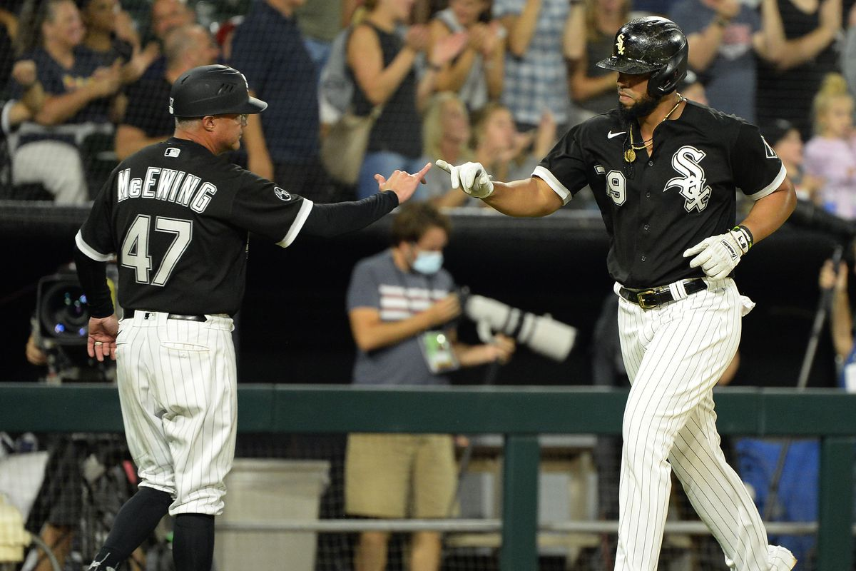 """Jose Abreu #79 celebrates with Third Base Coach Joe McEwing #47 of the Chicago White Sox after hitting a solo home run in the third inning against the Detroit Tigers on October 1, 2021 at Guaranteed Rate Field in Chicago, Illinois. The home run was Abreu""""u2019s 30th of the season, his fifth with at least 30 home runs and 100 runs batted in."""