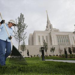 Temple Attendant Cara Gordon cares for the lawn in preparation for an open house at the Ogden Utah Temple in Ogden, Tuesday, July 29, 2014.