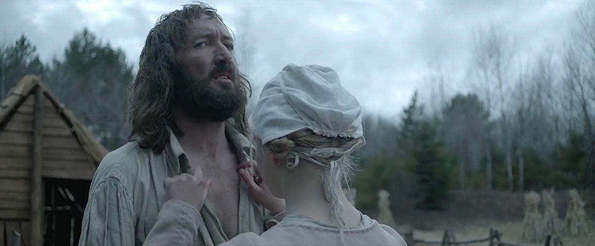 Ralph Ineson grimaces as Anya Taylor-Joy examines his chest in The Witch