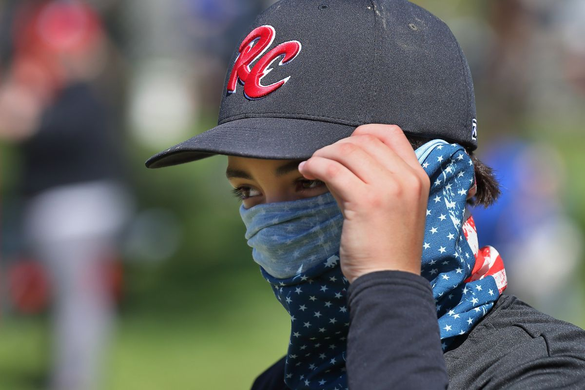 """In this Saturday, May 9, 2020 photo, St. Louis RiverCats youth baseball player Carter Herrin, 13, from House Springs, wears a face covering during the Mother's Day Classic baseball tournament organized by GameTime Tournaments in Cottleville, Mo.. """"His mom sent it with him"""" said Carter's dad Noah Herrin. Only a few players and coaches wore masks or face coverings during the tournament. (David Carson/St. Louis Post-Dispatch via AP)"""