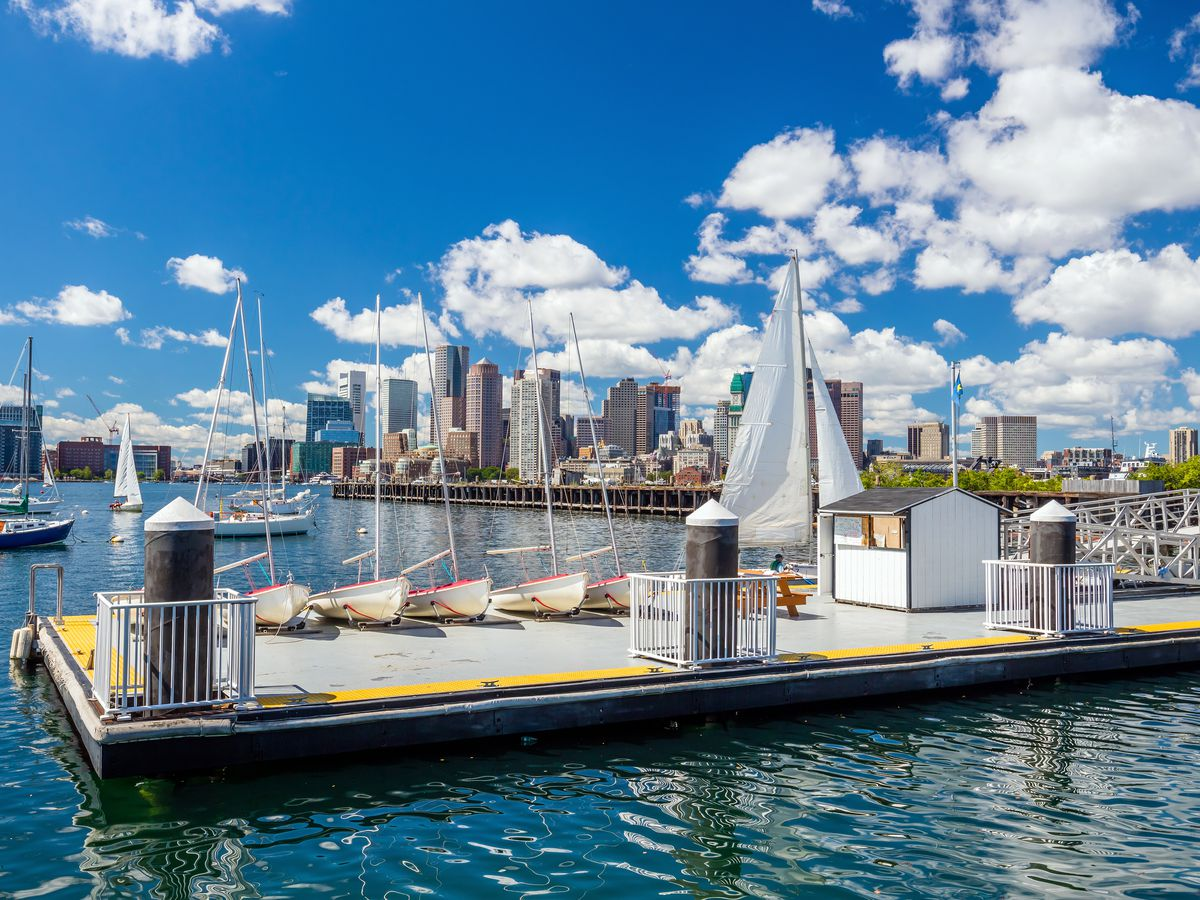 In the foreground is a pier at Piers Park in Boston. There are boats on the water. In the background is the city skyline of Boston with many tall buildings.