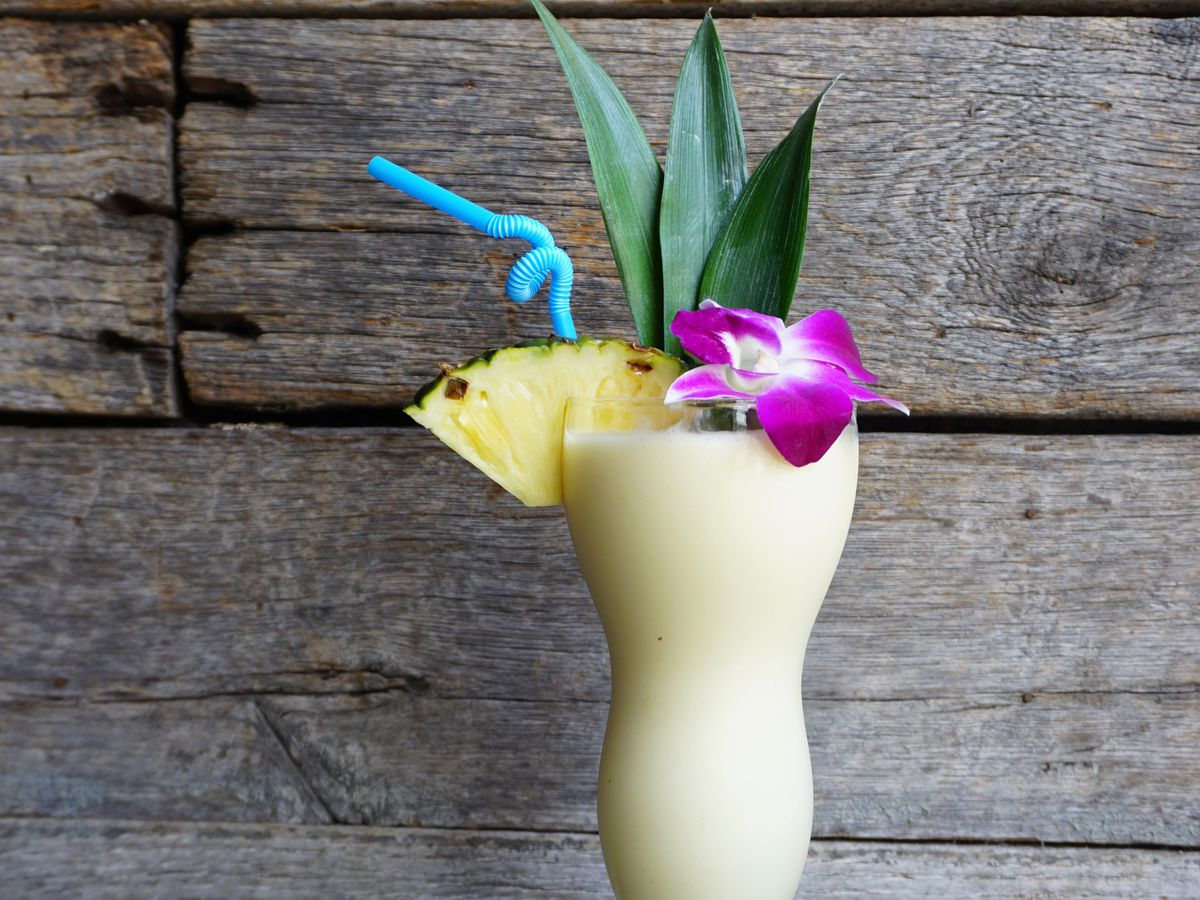 A frozen pina colada, pictured in front of a light wooden background, is garnished with an orchid, pineapple slice, and twisty blue straw