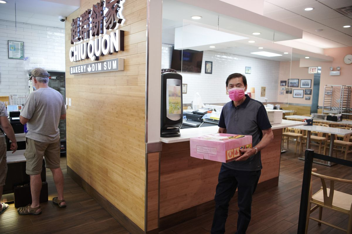 A person wearing a pink mask, holding a pink box of pastries inside a bakery.