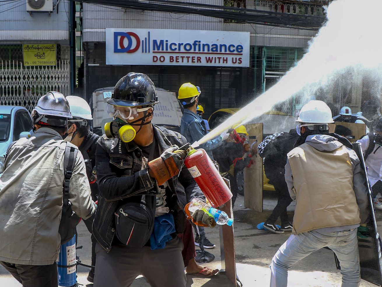 Anti-coup protesters discharge fire extinguishers to counter the impact of the tear gas fired by police during a demonstration in Yangon, Myanmar Thursday, March 4, 2021.
