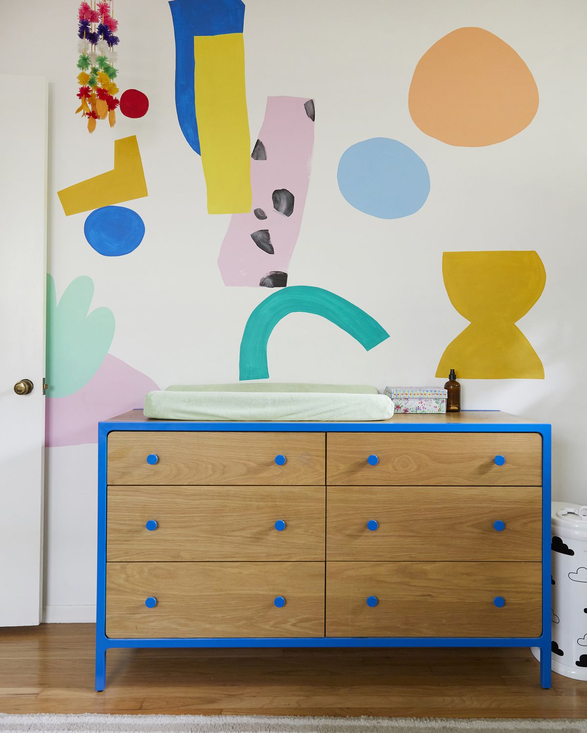 A wooden dresser with painted blue handles sits against a wall with a multitude of colorful painted shapes.