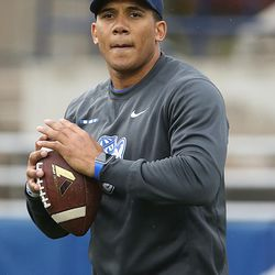 Safeties coach Preston Hadley throws to his players while warming up before the Blue-White game at LaVell Edwards Stadium in Provo on Saturday, April 7, 2018.