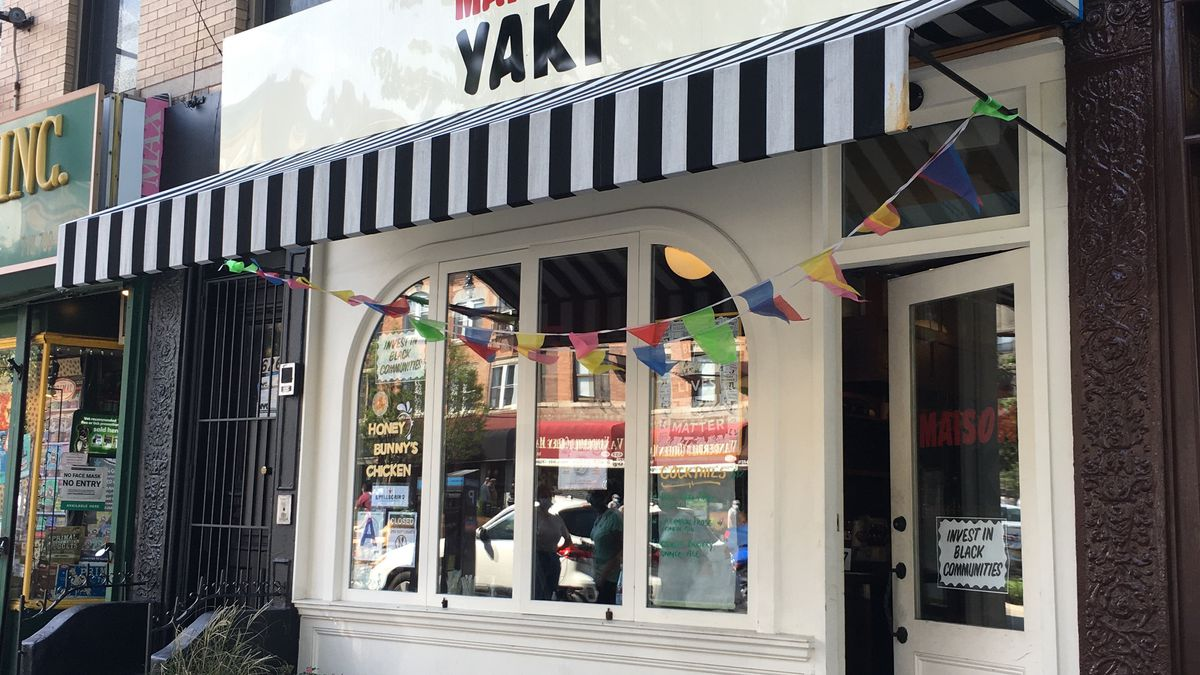 """The front of a restaurant with a striped awning, colorful flags, and a sign that reads """"Maison Yaki"""""""