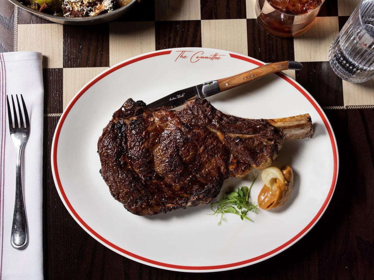 A large bone-in piece of steak on a oval platter beside a small dollop of sauce, on a checkerboard table