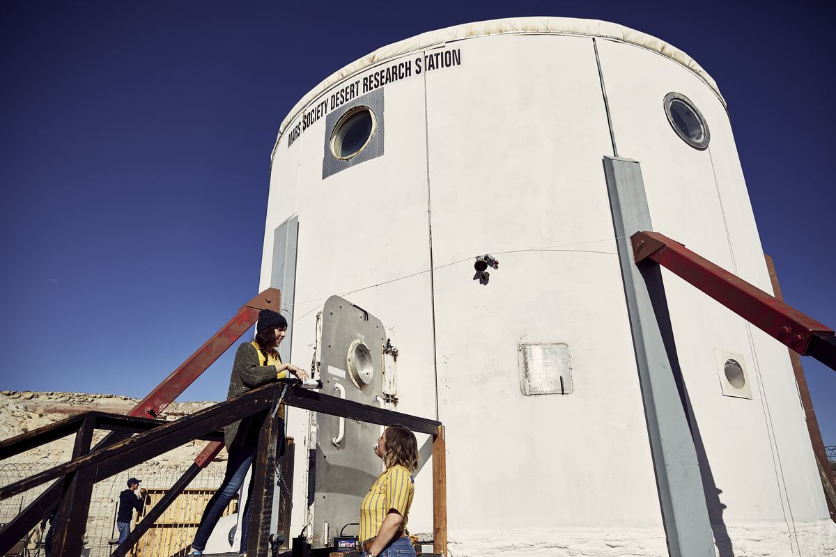 Exterior of white cylindrical dwelling in the desert.