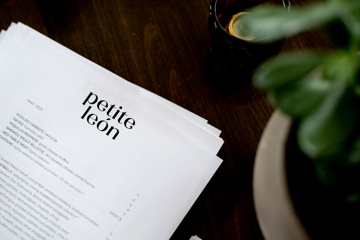 The paper menu on a black table with a green succulent nearby