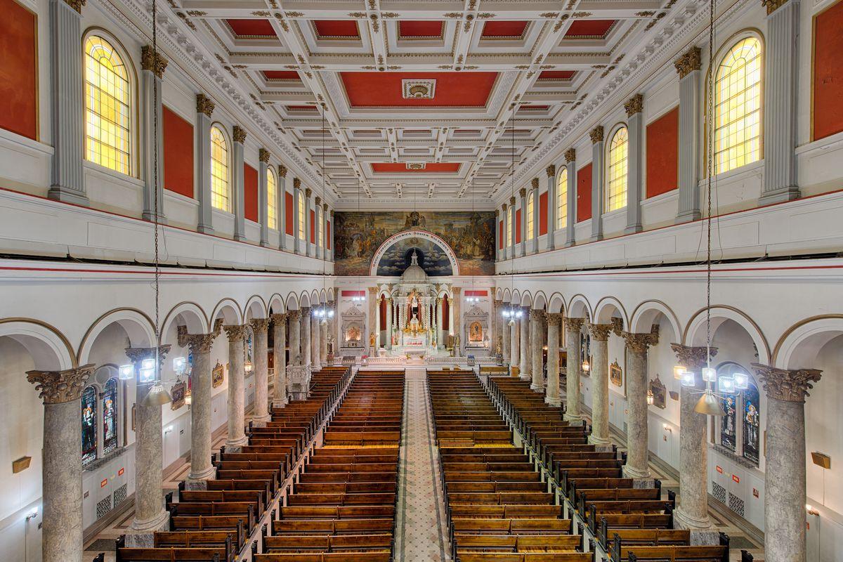A long rectangular church sanctuary with wooden pews, Renaissance Revival style details and columns.