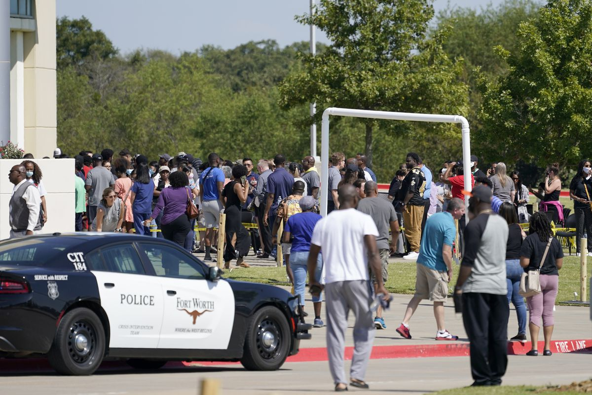 Families stand outside the Mansfield ISD Center for the Performing Arts waiting to be reunited with their children, Wednesday, Oct. 6, 2021 in Mansfield, Texas, following a shooting at the Timberview High School in Arlington.