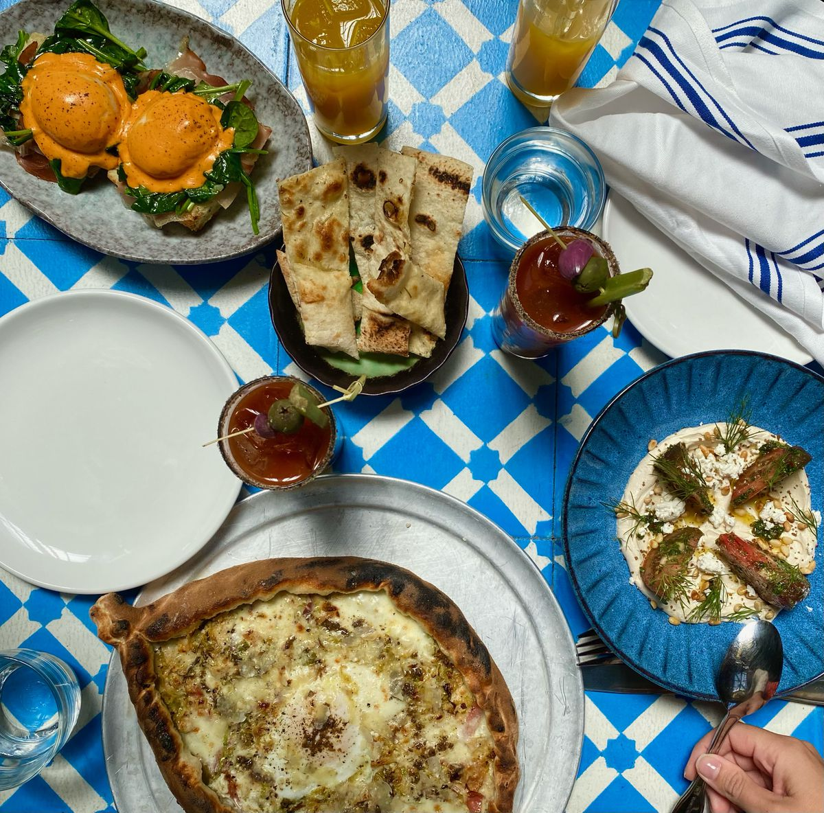 An overhead photograph of several dishes, including a pizza, eggs benedict, and a bowl of tahini and sliced tomato