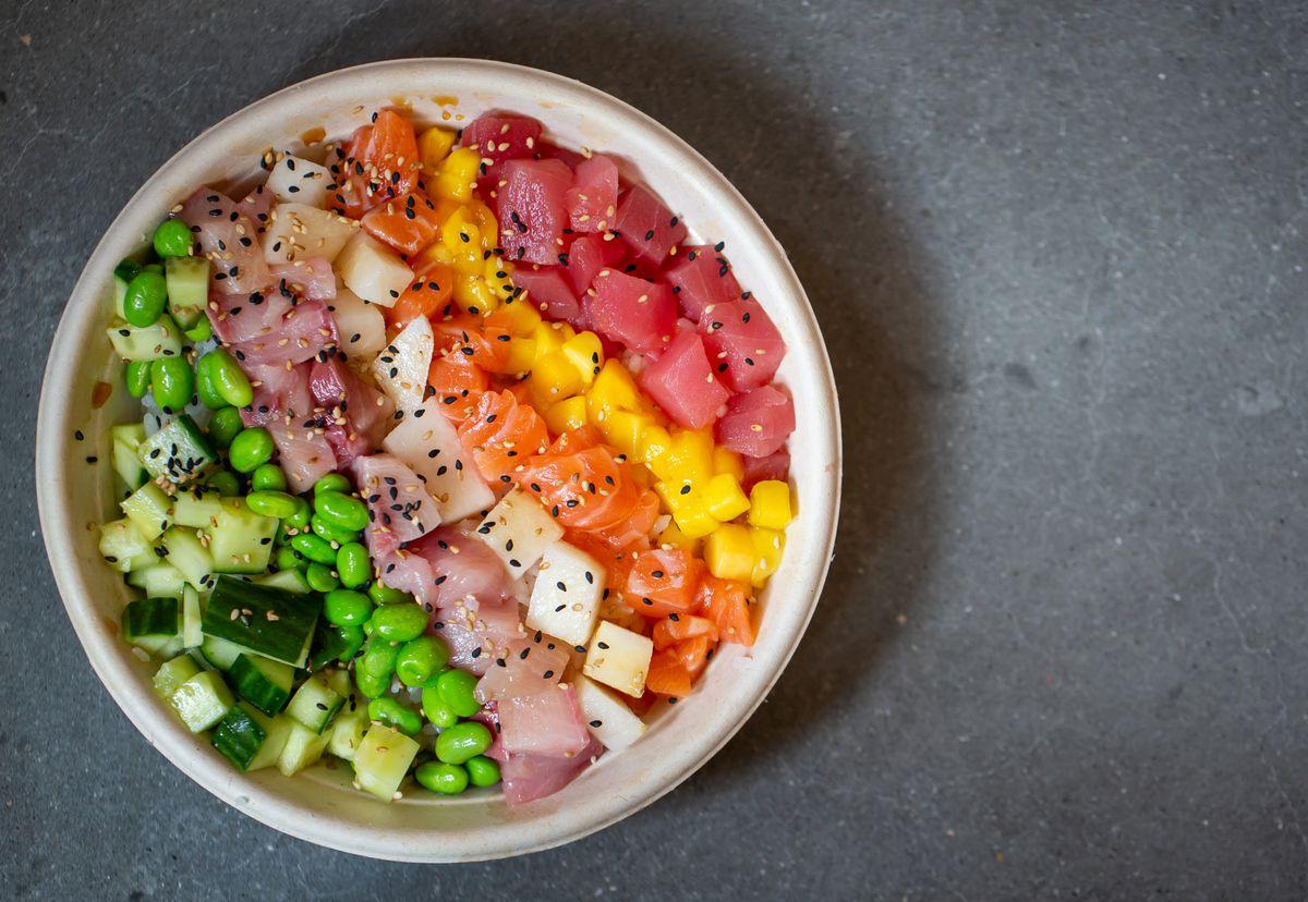 Poke bowl with tuna, mango, asian pear, cucumber, seaweed salad,  wasabi soy, spicy chili sauce