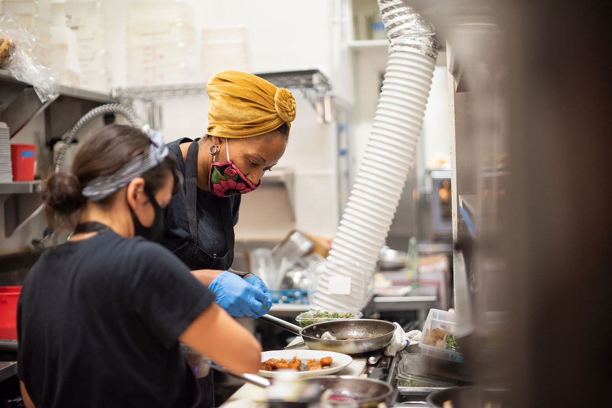 A female chef and employee work together on  dish inside of a kitchen.