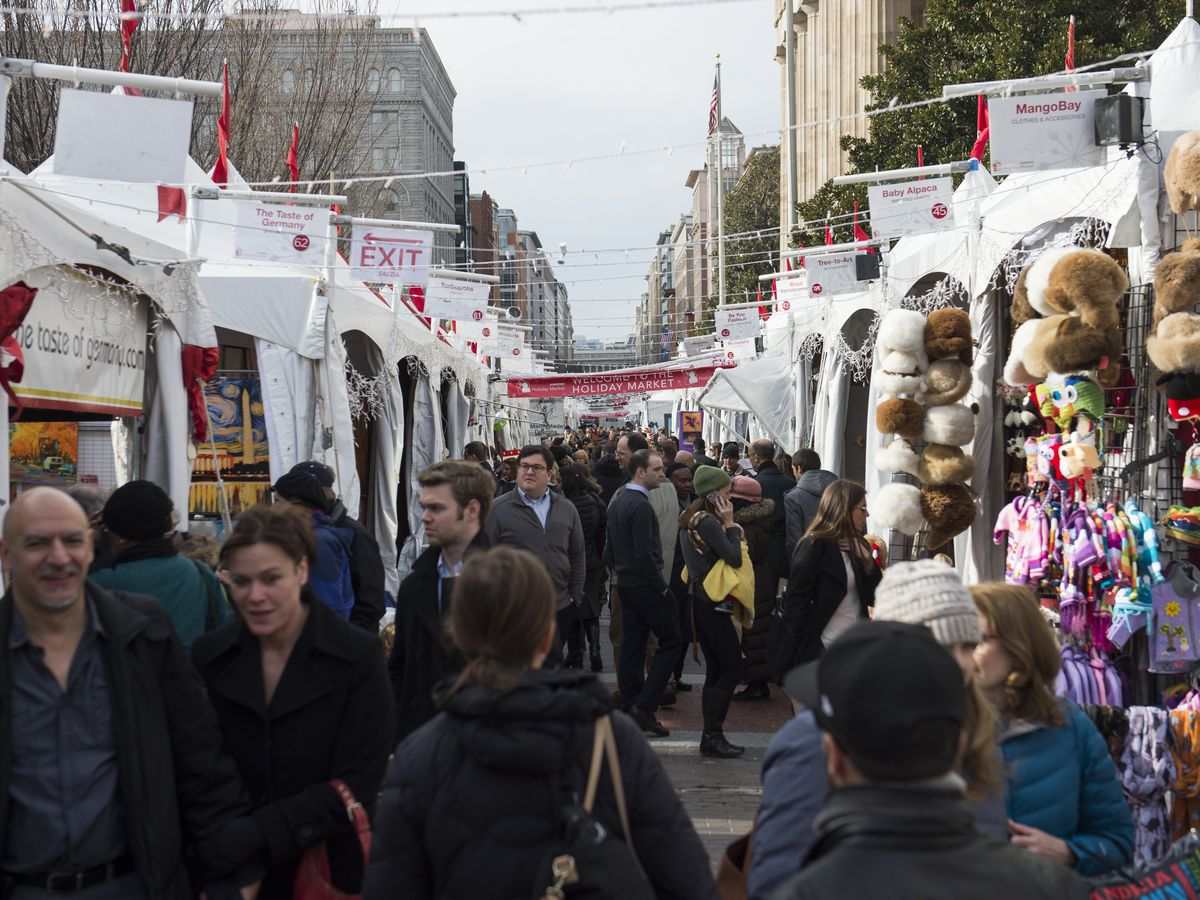 A holiday market filled with people in the middle of a city. The market is lined with white tents.