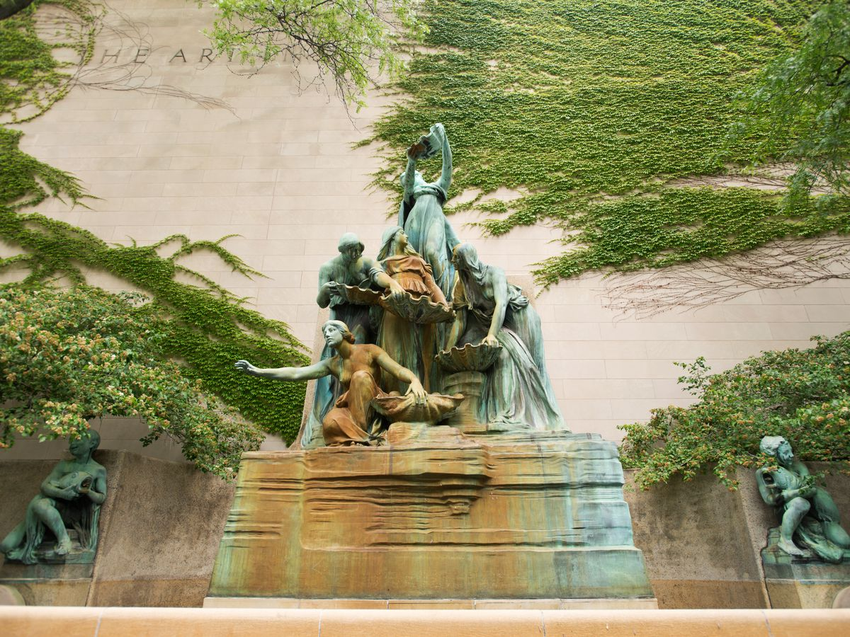 A water fountain called Fountain of the Great Lakes in Chicago. The fountain has a sculpture of a group of people with wash basins.