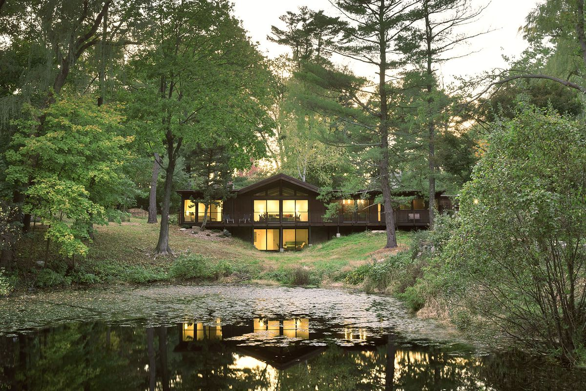 Exterior view of broad wooden house with extensive decking and pitched section set in the woods by a pond.