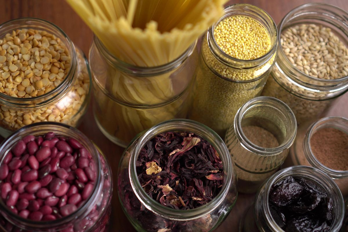 An aerial shot of glass jars containing rice, beans, pasta, tea, and other dry goods, on a light wood table.