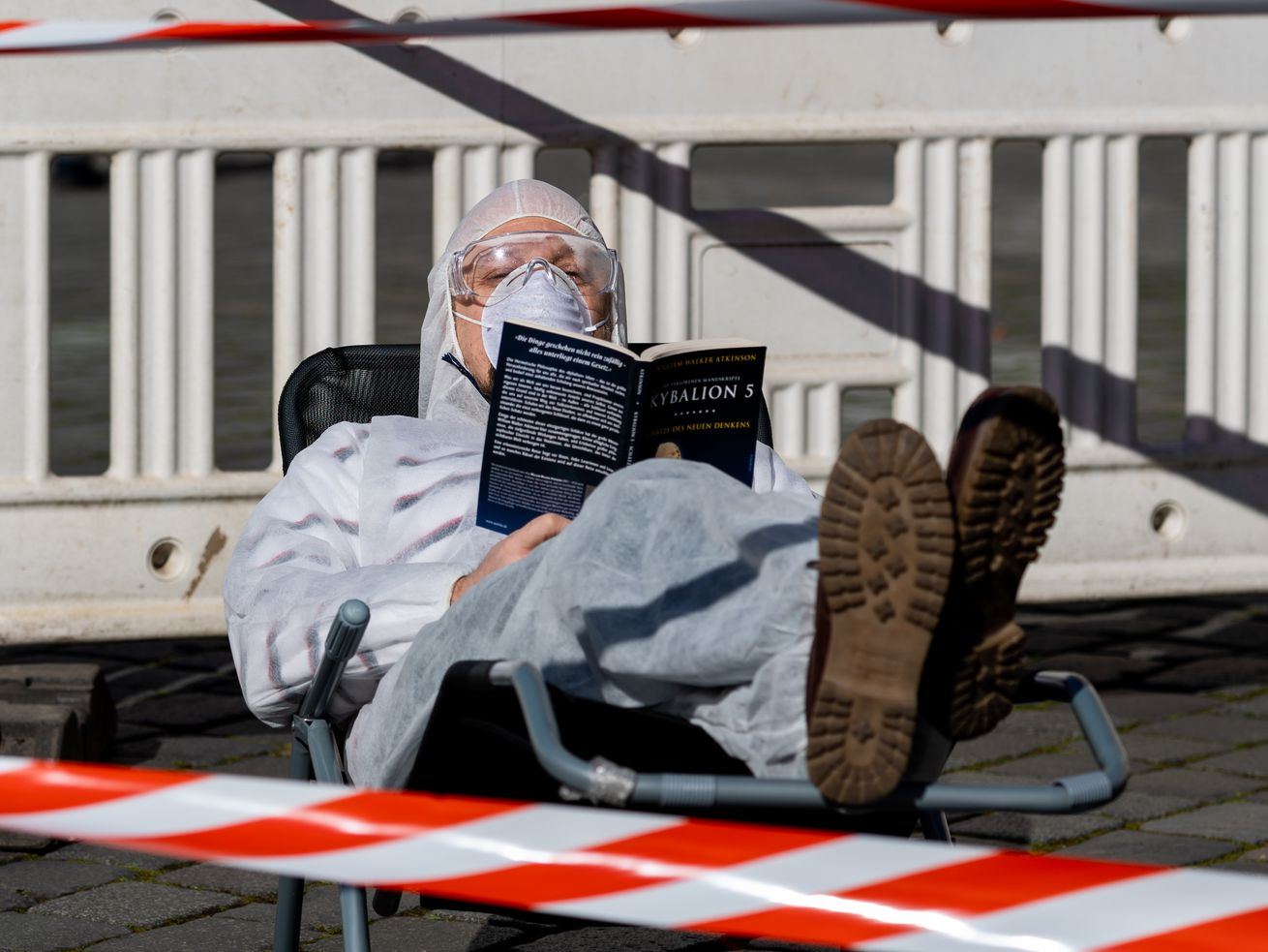 A Dresden resident lies on a sun lounger with a book, a mask, and protective clothing behind barrier tape.