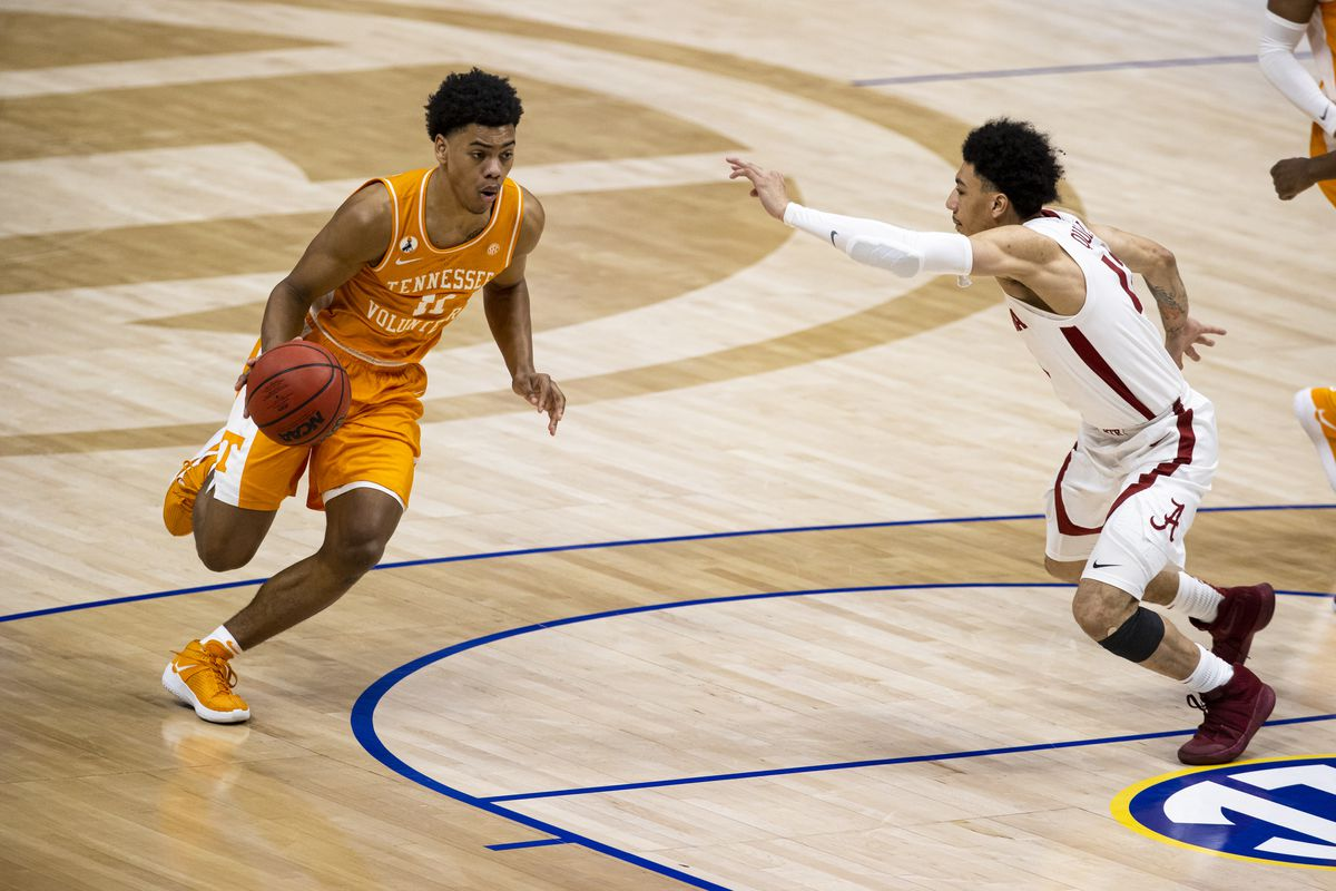 Jaden Springer of the Tennessee Volunteers drives to the basket against Jahvon Quinerly of the Alabama Crimson Tide during the first half of their semifinal game in the SEC Men's Basketball Tournament at Bridgestone Arena on March 13, 2021 in Nashville, Tennessee.