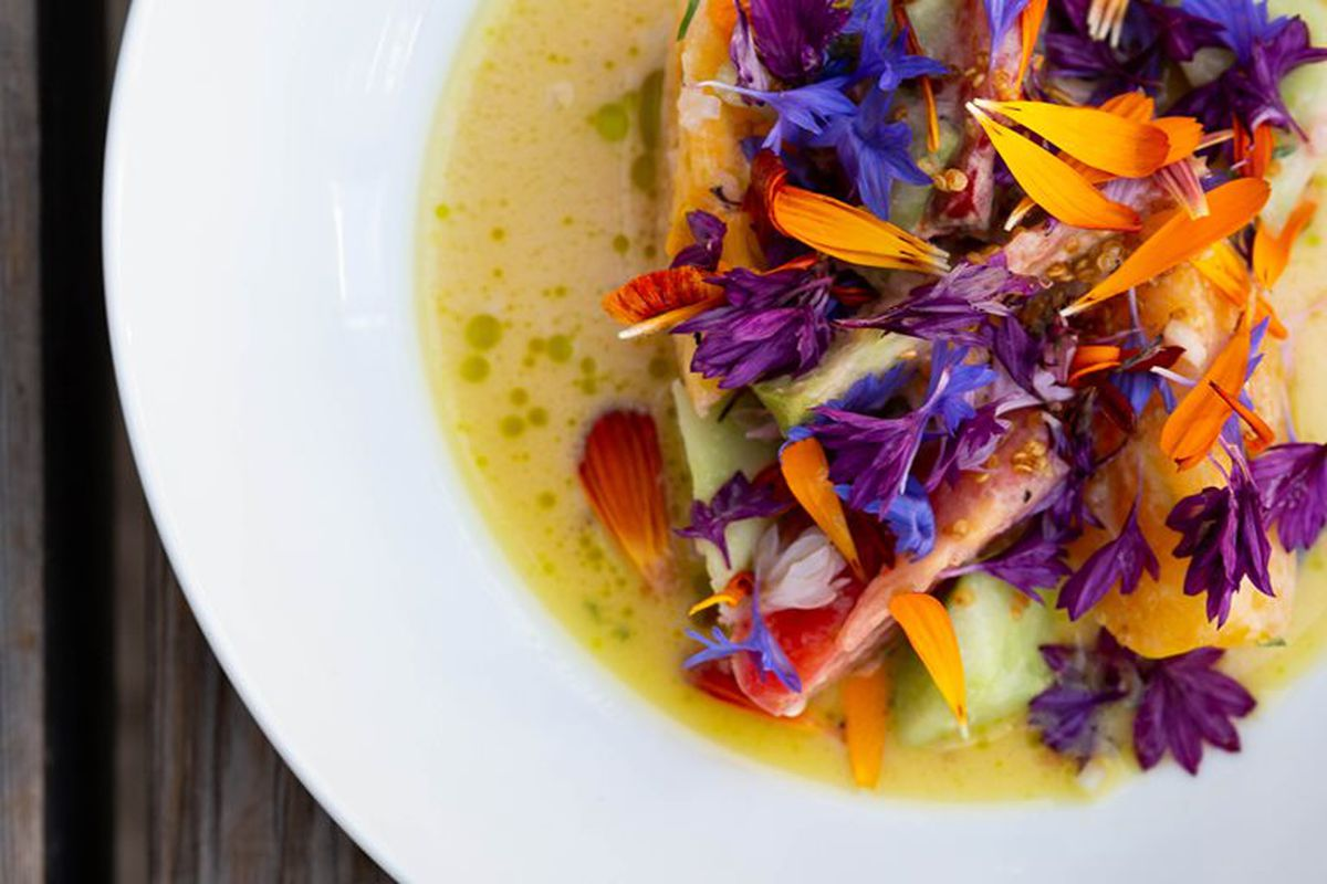 Heirloom tomatoes and bright flowers in a bowl with broth