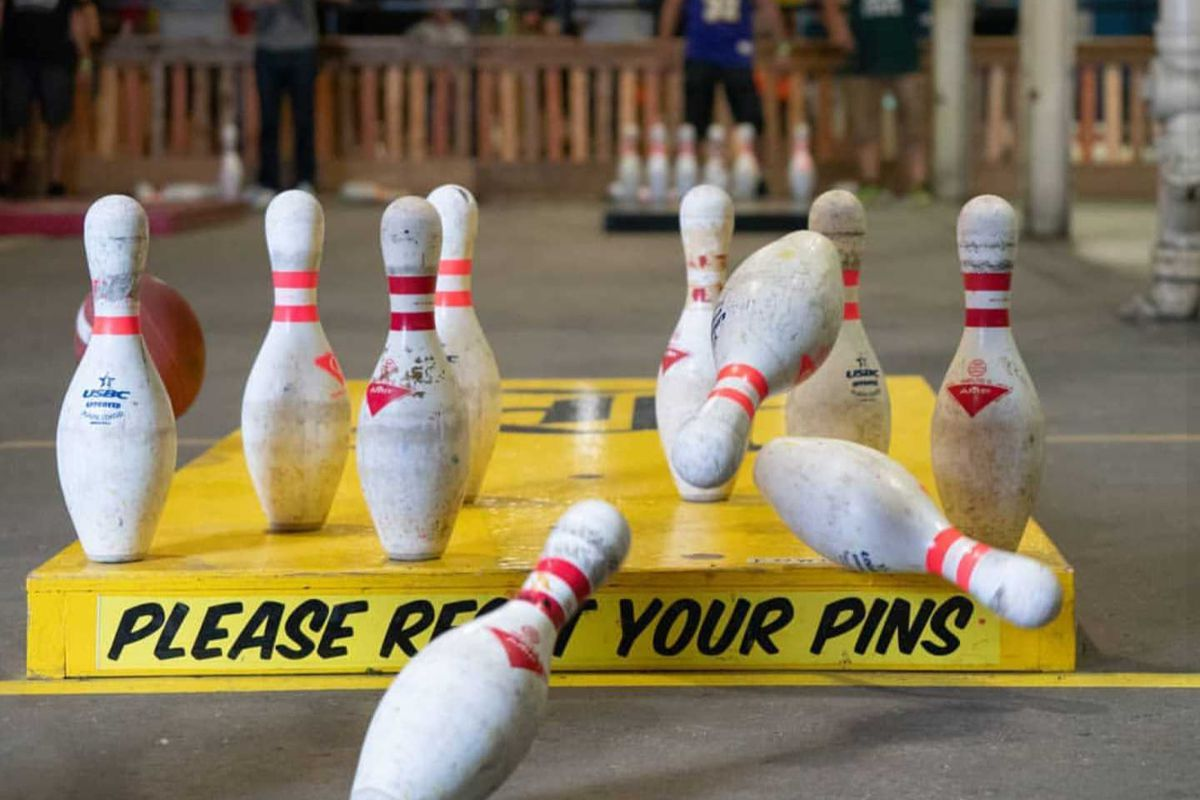 """A yellow wooden platform set with bowling pins, three falling bowling pins, and a black painted """"please reset your pins"""" sign"""