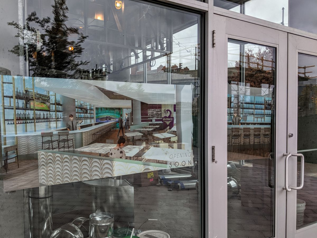 Renderings in the window of a construction site that will be home to a restaurant
