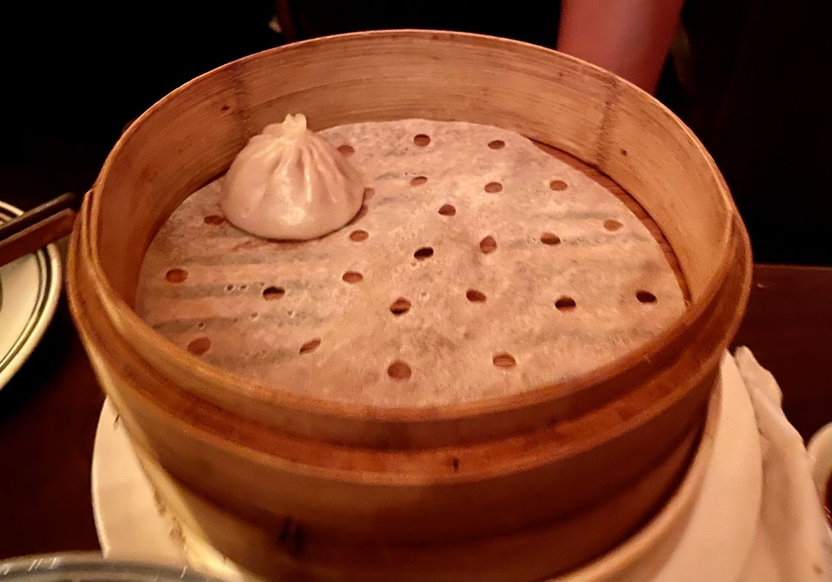 A blurry photograph of a lone soup dumpling sitting in a bamboo steamer at night