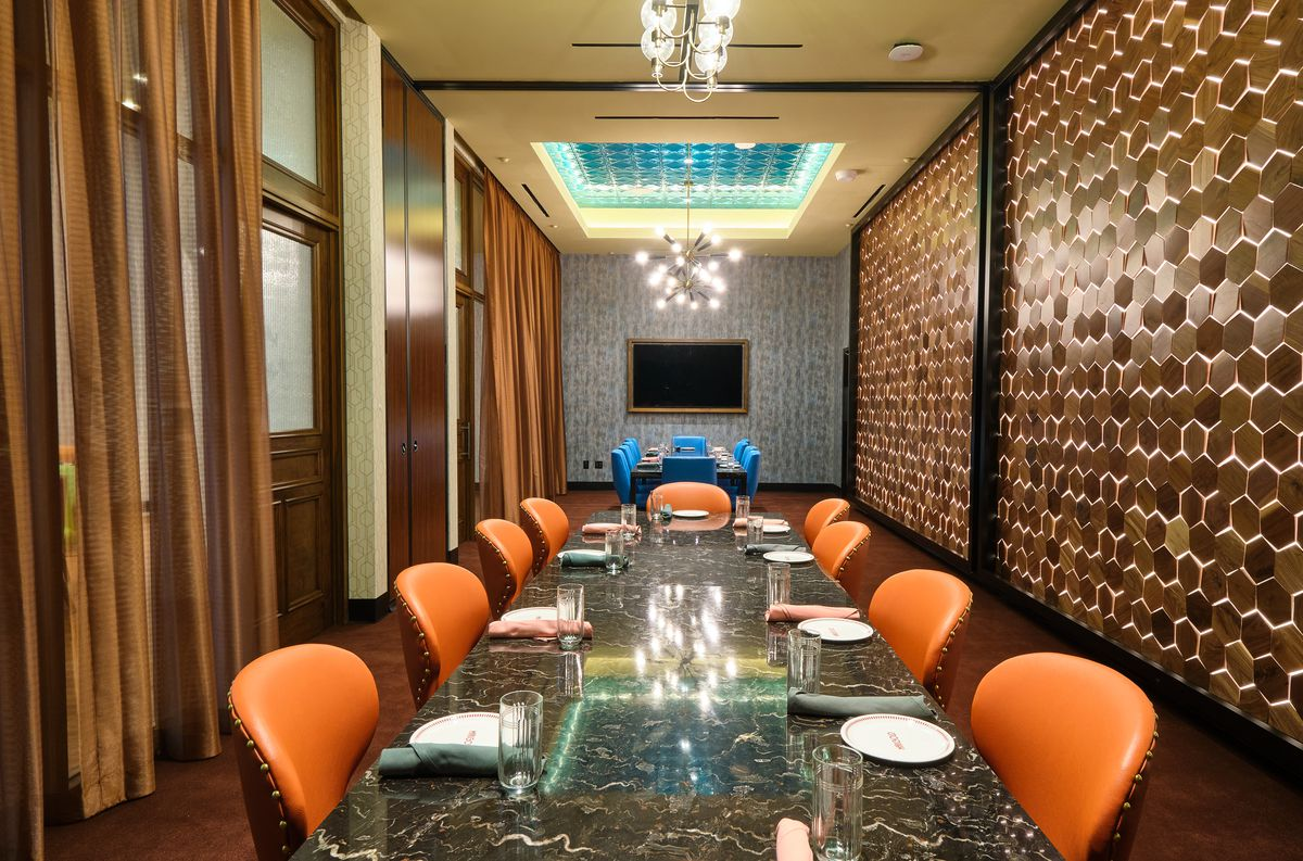 A long table with orange chairs