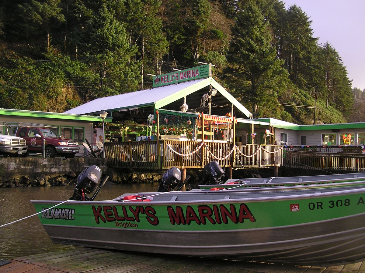 A lime-green crabbing boat is docked in front of a wooden house that's home to the marina.