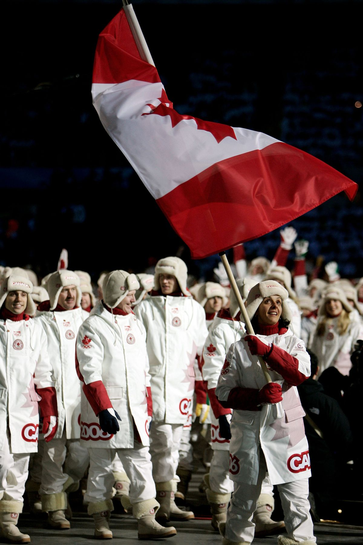 Danielle Goyette carries the Canadian flag during the Opening Ceremony of the Turin 2006 Winter Olympic Games