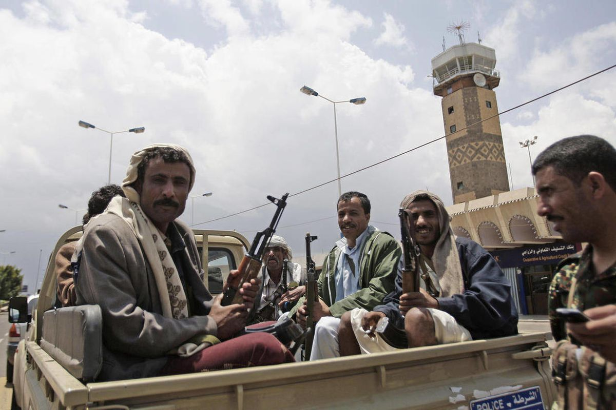Yemeni policemen sit in a pickup truck in front of Sanaa's International airport in Yemen, Sunday, April 8, 2012. Yemen's main airport reopened on Sunday, a day after gunmen loyal to the nation's former president seized the facility in the capital Sanaa,
