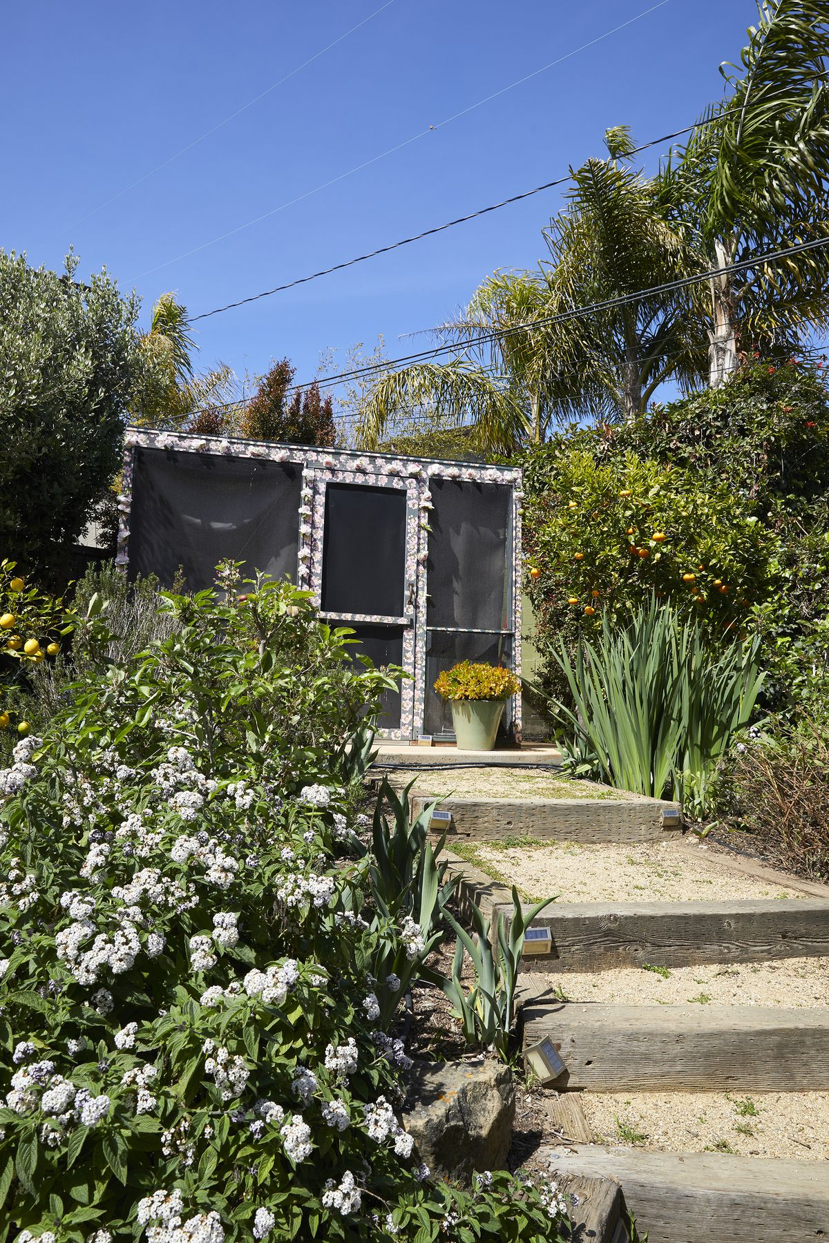 Stairs leading up to a structure which houses an outdoor bedroom. The stairs are flanked by flowering shrubbery.