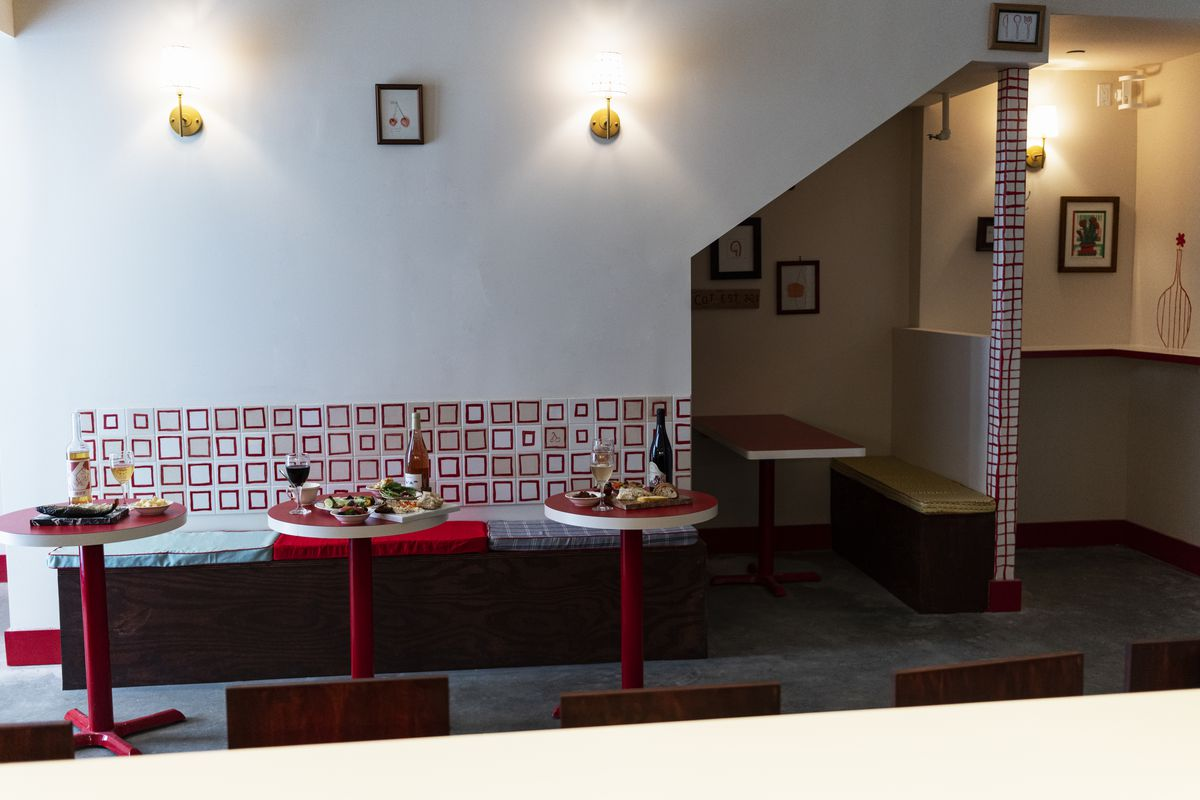 The interior of a restaurant with white walls, red tile, and three small tables with food set for service